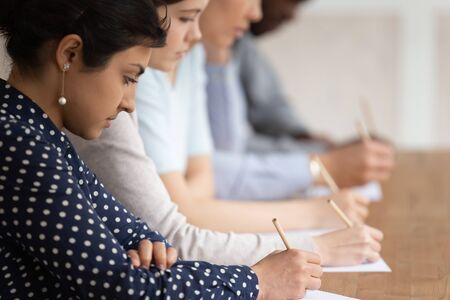 Foto de Multinational students seated at desk in row holding pencils writing on papers, take part in university exams, learning process or test of scholars knowledge skill in subject, higher education concept - Imagen libre de derechos