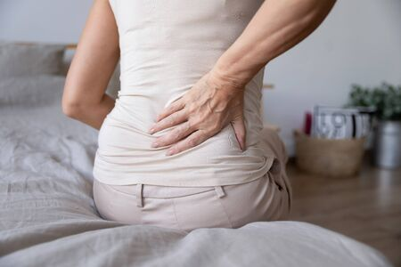 Foto de Old mature woman sit on bed touch back feel morning backpain suffer from lower lumbar discomfort muscle pain wake up with backache after sleep on uncomfortable mattress concept, close up rear view - Imagen libre de derechos