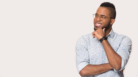 Foto de Smiling african American man in glasses isolated on grey studio background look at blank copy space vacant advertising place thinking, happy biracial male in spectacles pondering over good sale offer - Imagen libre de derechos