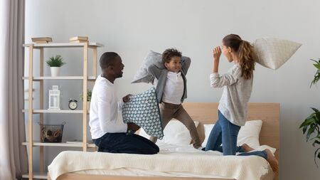 Photo pour Excited multiracial young family with little boy child have fun in bedroom engaged in pillow fight, overjoyed happy international mom and dad play with small son, enjoy weekend at home together - image libre de droit