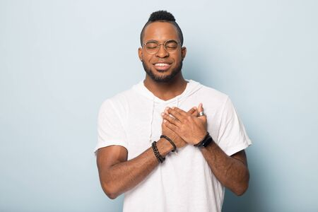 Foto de Smiling calm african American man in glasses isolated on blue studio background hold hands at heart chest praying, grateful biracial male believer feel happy peaceful, thanking god, faith concept - Imagen libre de derechos