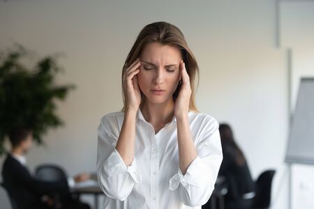 Stressed tired sad professional young business woman feeling sick headache at work standing in office, frustrated overworked female executive suffer from pain pressure migraine at workplace concept