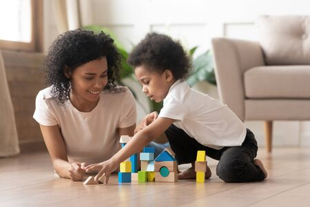 Photo pour Caring african American smiling mom or nanny lying on floor playing with little boy kid with toy blocks, happy loving black mother enjoy funny learning activity with toddler son with building bricks - image libre de droit