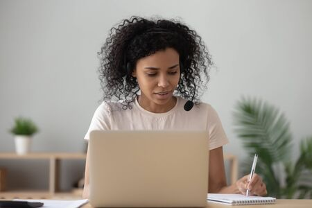 Foto de Concentrated african American female student in headset sit at desk study using laptop making notes, focused black woman in headphones watching webinar writing in notebook, distant education concept - Imagen libre de derechos