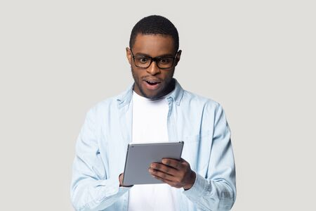 Foto de Head shot close up surprised African American man looking at computer tablet screen, young male using electronic device, reading unexpected news in email, shopping offer, isolated on grey background - Imagen libre de derechos
