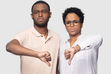 Head shot portrait close up unhappy African American couple in glasses showing thumbs down, looking at camera, dissatisfied man and woman giving negative feedback, isolated on grey background