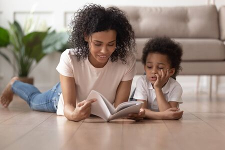 Photo pour Young african American mom lying on floor with cute toddler boy reading book at home together, black loving mother or nanny enjoy spending time with little son learning look at pictures in textbook - image libre de droit