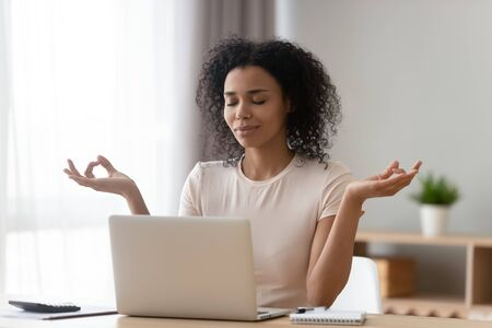 Foto de Calm African American woman meditating at desk with laptop, female working or studying at home, beautiful girl with closed eyes doing yoga exercise, breathing deep, stress relief concept - Imagen libre de derechos