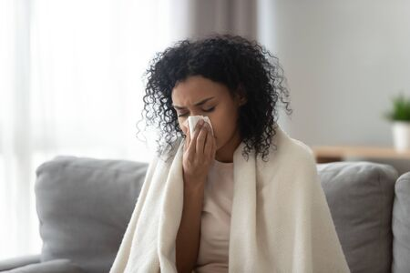 Foto de Sick African American woman covered warm blanket blowing running nose, feeling bad, suffering from fever, holding handkerchief, allergic reaction or seasonal infection, problem with health - Imagen libre de derechos
