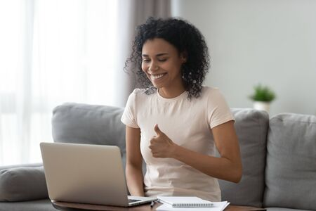 Foto de Smiling African American woman showing thumbs up, using laptop, making video call, satisfied student recommending distance education, teacher mentor recording webinar, working online at home - Imagen libre de derechos