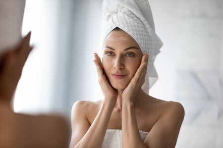Photo pour Beautiful young woman look in mirror massaging face applying cream in bathroom, pretty lady wrap towel on head put facial moisturizer lifting hydrating moisturizing creme, skin care treatment concept - image libre de droit