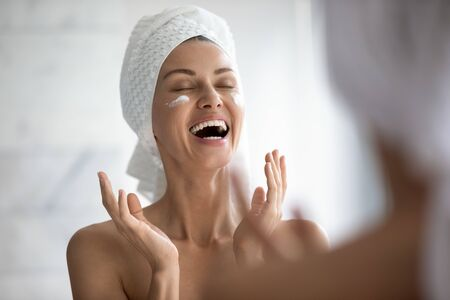 Photo pour Positive funny young woman laughing while applying facial cream reflecting in mirror, happy attractive lady put moisturizing nourishing creme doing morning routine in bathroom, skin care concept - image libre de droit
