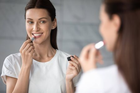 Photo pour Smiling young beautiful lady holding apply nude color lipstick on lips get ready in morning, happy sexy gorgeous attractive woman look in mirror doing make up routine put cosmetic on face in bathroom - image libre de droit