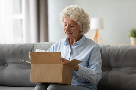 Photo pour Smiling elderly woman customer receive post shipment parcel at home, happy old senior grandma hold open cardboard box sit on sofa in living room, online shopping order fast courier delivery concept - image libre de droit