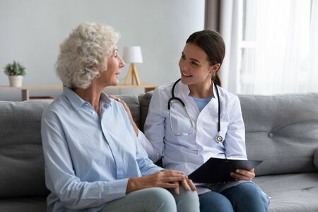 Photo for Caring young woman nurse help old granny during homecare medical visit, female caretaker doctor talk with elder lady give empathy support encourage patient sit on sofa older people healthcare concept - Royalty Free Image