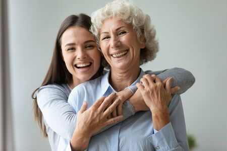 Foto de Cheerful affectionate two age generation women embracing indoor, happy young adult daughter granddaughter hug old retired grandmother mom laughing bonding looking at camera at home, family portrait - Imagen libre de derechos