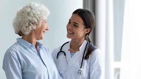 Photo for Smiling caring young female nurse doctor caretaker assisting happy senior grandma helping old patient in rehabilitation recovery at medical checkup visit, elder people healthcare homecare concept - Royalty Free Image