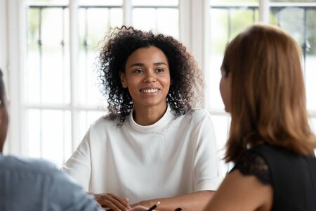 Photo pour Smiling african american young businesswoman talking with diverse clients or partners at business meeting in office. Happy mixed race female hr manager conducting job interview with applicants. - image libre de droit