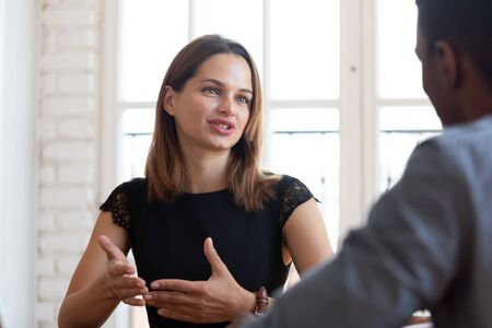 Photo pour Head shot focus on happy pleasant young female financial advisor realtor lawyer explaining contract details to concentrated thoughtful african american male client at meeting in company office. - image libre de droit
