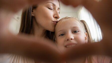 Foto de Head shot close up portrait affectionate 30s mommy kissing small preschool smiling daughter, making love sign. Happy young loving mother bonding little kid girl, showing heart gesture with hands. - Imagen libre de derechos