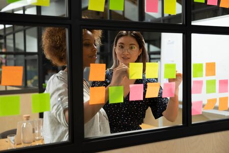 Photo pour Concentrated african american young female scrum master working together with smart vietnamese businesswoman colleague, putting notes on sticky paper at window glass agile kanban board at office. - image libre de droit