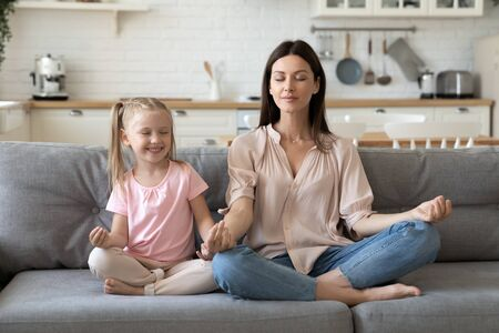 Foto de Front view mindful calm 30s woman sitting in lotus pose with cute little daughter on comfortable sofa in living room. Smiling preschool girl practicing yoga breathing exercises with mommy at home. - Imagen libre de derechos