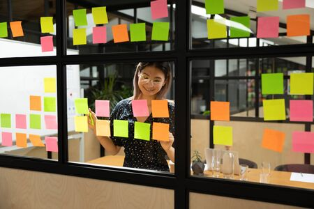 Foto de Smiling asian female project manager in eyewear organizing working process at glass window kanban board. Happy vietnamese employee adding paper stickers with tasks, improving managing ideas at office. - Imagen libre de derechos