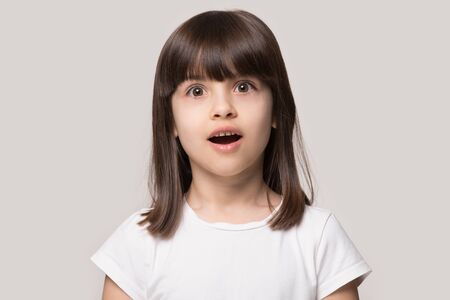 Photo pour Close up head shot portrait with surprised little brown-haired girl. Concept happy activity playful kid opened mouth in amaze on gray background, six year child looking at camera and posing. - image libre de droit