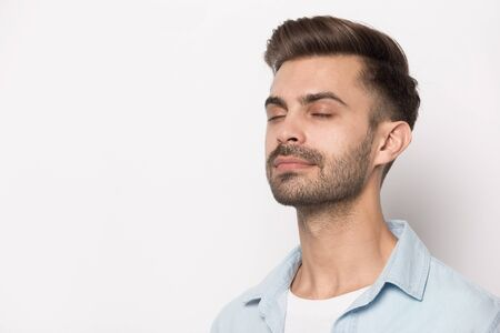 Photo pour Close up head shot image of peaceful handsome bearded man near copy space for ad presentation. Successful entrepreneur relaxing feels happy breathing fresh air. Employee meditation concept. - image libre de droit