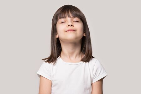 Photo pour Close up head shot portrait image with relaxed little brown-haired girl, reduce stress. Wellbeing concept rest kid meditating and deep breathing on gray background, six year child with eyes closed - image libre de droit