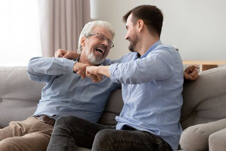 Photo pour Happy old senior father and son fists bumping, celebrating success or greeting each other, mature aged dad and millennial man having fun together, sitting on couch at home, enjoying weekend - image libre de droit