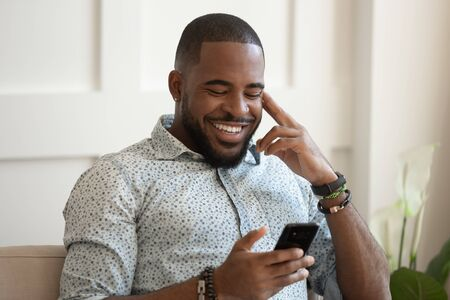 Foto de Smiling african American millennial man sit on couch at home texting messaging on smartphone, happy biracial young male relax use cellphone, browse internet, chat having pleasant conversation - Imagen libre de derechos