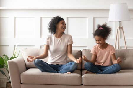 Photo pour Mixed-race mother little daughter distracted from meditation laughing sit in lotus position on couch in living room, mom teach kid beginner yoga asana, healthy life habits, activities at home concept - image libre de droit