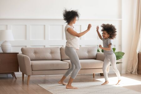 Photo pour Excited young african American mom or nanny play dancing with funny little preschooler girl child, happy biracial mother parent have fun entertain with small daughter jump move to rhythm at home - image libre de droit