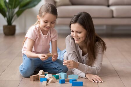 Photo pour Young happy mom and preschooler daughter sit on floor playing with toy blocks together, smiling mother or nanny and little girl child have fun engaged in funny activity game with building bricks - image libre de droit