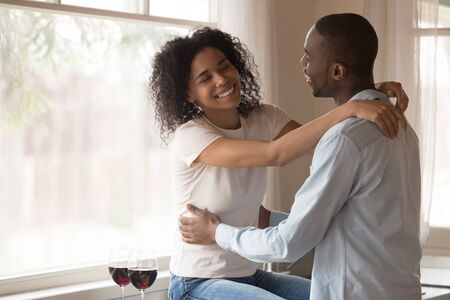 Foto de Loving smiling african American millennial couple hug relax at home kitchen drinking wine celebrating anniversary, happy biracial husband and wife cuddle embrace enjoy romantic date together - Imagen libre de derechos