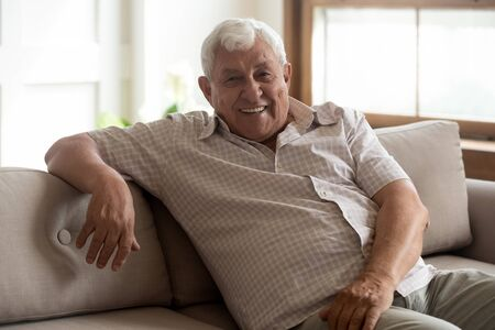 Photo for Portrait of happy 80s retired man, sitting on couch at home. Smiling healthy elder grandfather relaxing on sofa at living room, enjoying leisure free time. Pleasant male pensioner posing for photo. - Royalty Free Image