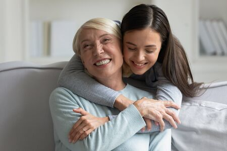 Photo for Grown up daughter strong cuddle loving 60s mother close up view, different generations women spend time in living room enjoy moment of caress and closeness having warm relation, giving support concept - Royalty Free Image