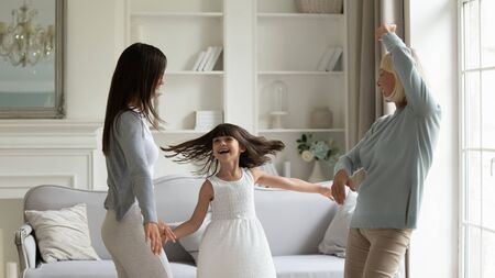Photo pour Elderly 50s grandmother her grown up daughter and granddaughter fool around spend weekend together standing in modern living room dancing moving enjoy life, funny activities having fun at home concept - image libre de droit