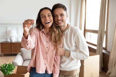 Photo pour Happy young family couple holding key to new home on moving day concept, first time real estate owners man husband embrace woman wife look at camera proud buying property stand in own flat with boxes - image libre de droit
