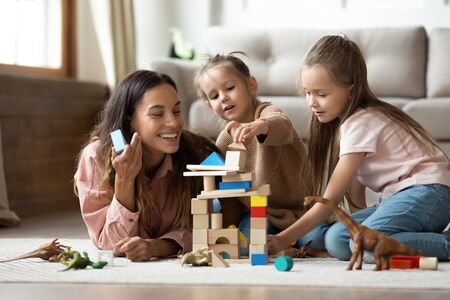 Foto de Happy young mum babysitter helping playing game with little kids daughters on floor, female nanny mother and cute small children sisters building castle of wooden blocks having fun with toys at home - Imagen libre de derechos