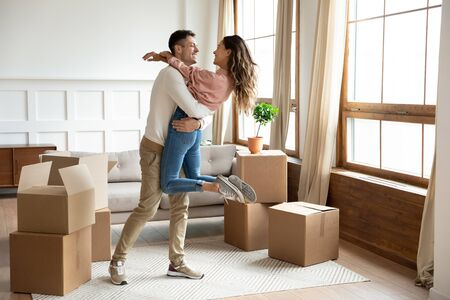 Photo pour Happy young husband lifting excited wife celebrating moving day with cardboard boxes, proud overjoyed family couple first time home buyers renters owners having fun enjoy relocation, mortgage concept - image libre de droit