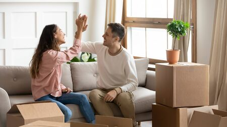 Photo pour Happy proud millennial couple give high five celebrate family goal achievement moving into new home, young family roommates tenants renters owners sit on sofa with boxes relocate in own house concept - image libre de droit