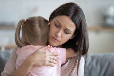 Photo pour Worried young foster care parent mother comforting solacing embrace adopted little child daughter give care and protection at home, loving concerned adult mom hug sad small girl consoling kid concept - image libre de droit