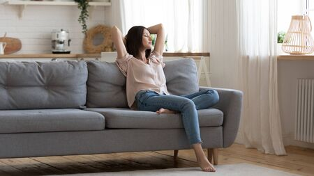 Photo for Serene lady housewife lounge sit on sofa feel fatigue napping hold hands behind head, calm young woman rest on comfort couch with eyes closed breath fresh air in cozy clean modern living room at home - Royalty Free Image
