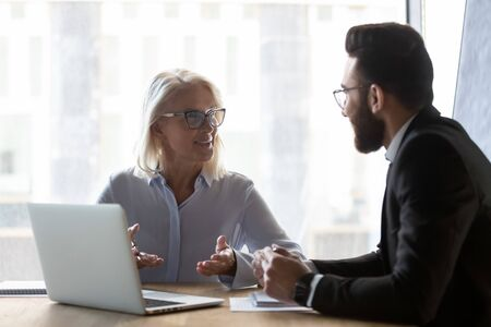 Photo pour Middle-aged Caucasian woman talk share ideas with young male colleague discussing project in office, mature businesswoman speak considering cooperation with man coworker, use laptop at meeting - image libre de droit