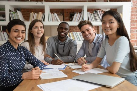 Photo for Happy mixed race students gathered in classroom, looking at camera. Smiling group of diverse young people holding video call lecture with abroad online course professor, ready to write down notes. - Royalty Free Image