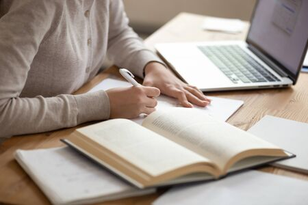 Foto de Close up female student sitting at desk, writing down notes from opened textbook and laptop. Young girl preparing for university session, exams, doing homework, paperwork, writing coursework or essay. - Imagen libre de derechos