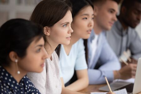 Photo for Focused group of mixed race students sitting together at lecture, carefully listening to teacher or trainer at college. Concentrated attentive diverse teammates listening to material explanation. - Royalty Free Image