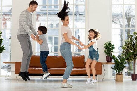 Foto de Playful young family with preschooler kids have fun engaged in funny activity at home, excited smiling parents and cute small children jumping in modern light living room, enjoy day off together - Imagen libre de derechos